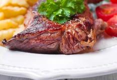Bife, batatas fritas e vegetais grelhados Fotos de Stock