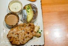 Bife, batatas fritas e vegetais grelhados da carne de porco A carne classificada da carne de porco e dos vários vegetais na grad fotografia de stock