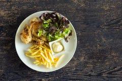 Bife, batatas fritas e vegetais grelhados da galinha na tabela Foto de Stock Royalty Free