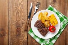 Bife com batata, milho, salada e o tomate grelhados Imagem de Stock Royalty Free