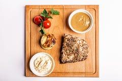 Bife com molho de mostarda em uma placa de madeira Fotografia de Stock Royalty Free