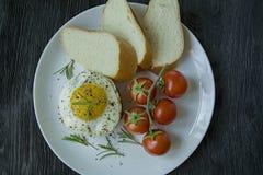 Bife com o ovo frito nas especiarias Decorado com alecrins, a cereja fresca e as fatias de p?o Arquivado em uma placa branca escu imagens de stock