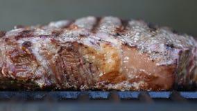 Bife cozinhado na grade com cintilação das chamas filme