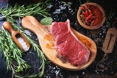 Bife cru com ervas e pimenta Fotos de Stock