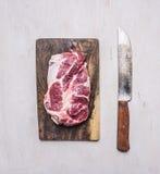 Bife cru delicioso da carne de porco em uma placa de corte com uma faca para o fim rústico de madeira da opinião superior do fund fotografia de stock