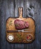 Bife cru do ribeye em uma placa de corte com uma forquilha, com sal dos alecrins e pimenta no fundo de madeira rústico, vista sup Fotos de Stock Royalty Free