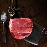 Bife cru em uma placa de corte, em uma faca e em umas especiarias perfumadas nas duas colheres do vintage Imagens de Stock