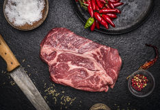 Bife cru fresco com a faca de cinzeladura da bandeja de sal da pimenta vermelha em um fim rústico escuro da opinião superior do f Fotografia de Stock
