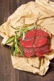 Bife cru fresco com pimentas, alecrins, sal no fundo de madeira Fotografia de Stock Royalty Free