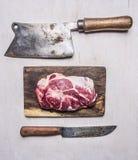 Bife cru fresco, delicioso da carne de porco em uma placa de corte com um talhador de carne e um fim rústico de madeira da opiniã Fotos de Stock Royalty Free