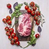 Bife cru fresco, delicioso da carne de porco em uma placa de corte com vegetais, fim rústico de madeira da opinião superior do fu Imagens de Stock