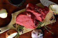 Bife cru fresco na placa de corte de madeira, vista superior fotos de stock