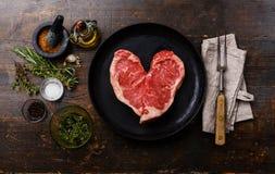 Bife da carne crua da forma do coração com ingredientes fotografia de stock