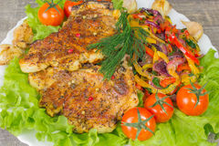 Bife da carne de porco com opinião dos tomates e do aneto de uma alface da forquilha Fundo cinzento do alimento na tabela de made Imagem de Stock