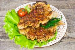 Bife da carne de porco com os tomates de uma alface da forquilha e opinião lateral do aneto Tabela de madeira do fundo cinzento d Fotografia de Stock