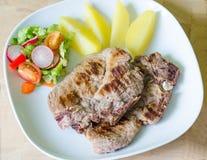Bife da carne de porco com salada e batatas Fotos de Stock