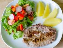 Bife da carne de porco com salada e batatas Foto de Stock Royalty Free