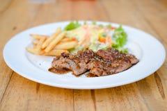 Bife da carne de porco na placa na tabela Imagem de Stock