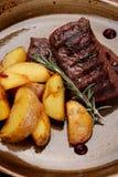 Bife da carne e alecrins grelhados das batatas na placa imagem de stock