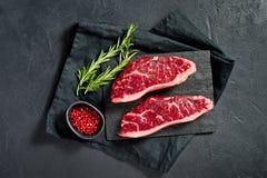 Bife da carne marmoreada Angus preto Fundo preto, vista superior fotografia de stock