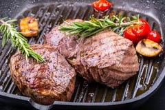 Bife da grade Bifes do lombo suculentos da carne grossa das parcelas na bandeja do Teflon da grade ou na placa de madeira velha imagens de stock
