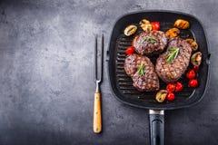 Bife da grade Bifes do lombo suculentos da carne grossa das parcelas na bandeja do Teflon da grade ou na placa de madeira velha imagem de stock