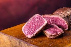 Bife da grade Bifes do lombo suculentos da carne grossa das parcelas na bandeja do Teflon da grade ou na placa de madeira velha foto de stock
