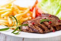 Bife de carne grelhado com fritadas francesas imagens de stock