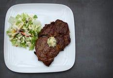 Bife de Ribeye com manteiga do coentro e uma refeição lateral do keto da salada Fotografia de Stock