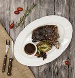 Bife de Ribeye da carne de mármore da carne com vegetais e molho de assado Servido em uma placa da pedra preta com forquilha e fa Foto de Stock
