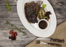 Bife de Ribeye da carne de mármore da carne com vegetais e molho de assado Servido em uma placa da pedra preta com forquilha e fa Fotos de Stock