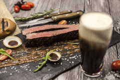 Bife de Ribeye da carne de mármore da carne com vegetais e molho de assado Servido em uma placa da pedra preta com forquilha e fa Imagens de Stock