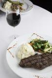 Bife de tira de New York com batatas e os legumes misturados triturados Imagens de Stock