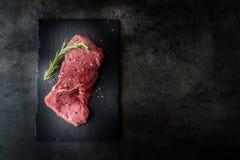 Bife de traseiro Bife cru da carne Melhore o bife cru com o carniceiro e a forquilha dos alecrins da pimenta de sal imagem de stock