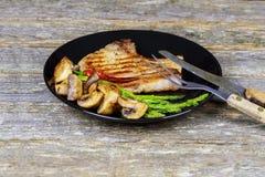 Bife do churrasco na bandeja com cogumelos e aspargo cozinhando em uma cozinha, carne deliciosa, picante, suculenta com o close u Imagem de Stock Royalty Free