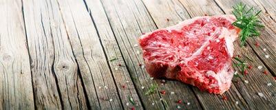Bife do lombo cru em de madeira com alecrins Fotografia de Stock Royalty Free
