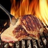 Bife do lombo de carne de porco na grade flamejante quente do assado com forquilha Foto de Stock Royalty Free