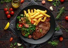 Bife do lombo grelhado com fritadas da batata e vegetais, salada do tomate em uma placa preta Tabela rústica imagem de stock royalty free