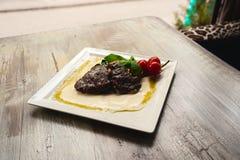 Bife e cogumelos grelhados com os tomates na placa branca Foto de Stock Royalty Free