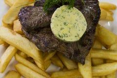 Bife e microplaquetas com manteiga de alho Foto de Stock