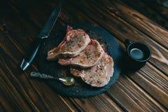 Bife e temperos crus da carne de porco da carne fresca na ard?sia de madeira escura da placa do fundo com faca do mel imagens de stock