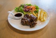 Bife e vegetais grelhados da carne de porco placa da carne de porco grelhada com batatas fritas e salada na tabela Corte grelhado fotos de stock royalty free
