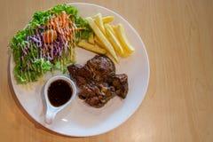 Bife e vegetais grelhados da carne de porco placa da carne de porco grelhada com batatas fritas e salada na tabela Corte grelhado fotografia de stock royalty free