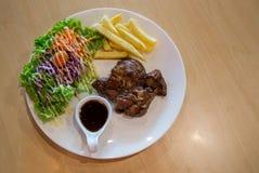 Bife e vegetais grelhados da carne de porco placa da carne de porco grelhada com batatas fritas e salada na tabela Corte grelhado imagem de stock