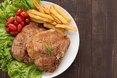 Bife e vegetais grelhados de costeleta da carne de porco com batatas fritas na madeira Fotografia de Stock Royalty Free