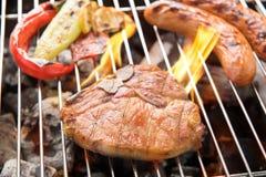 Bife e vegetal de costeleta da carne de porco com salsicha em um gril flamejante do BBQ Imagem de Stock Royalty Free