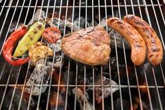 Bife e vegetal de costeleta da carne de porco com salsicha em um gril flamejante do BBQ Fotos de Stock