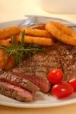 Bife grelhado com anéis de cebola imagens de stock royalty free