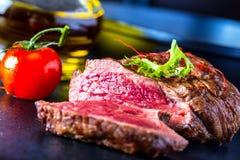 Bife grelhado com decoração vegetal Carne de vaca grelhada na placa da ardósia fotografia de stock