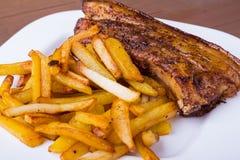 Bife grelhado cortado de Striploin do assado dos refor?os de carne de porco com o molho e a batata do chimichurri livres na placa imagem de stock royalty free